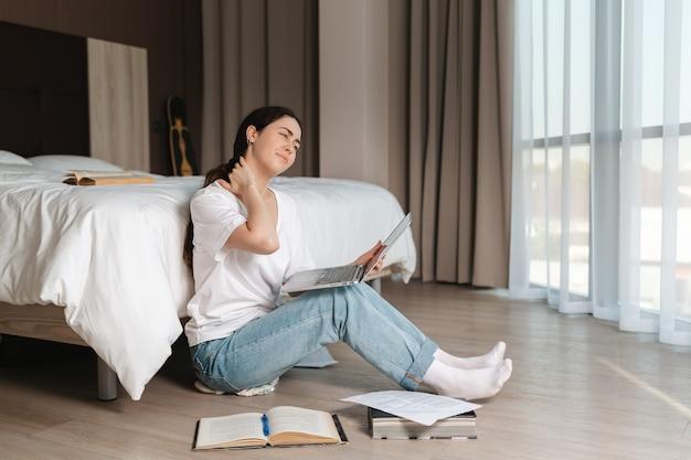 Uma jovem cansada faz uma massagem no pescoço enquanto trabalhava em seu laptop. interior da casa. o conceito de aprendizagem e trabalho online.