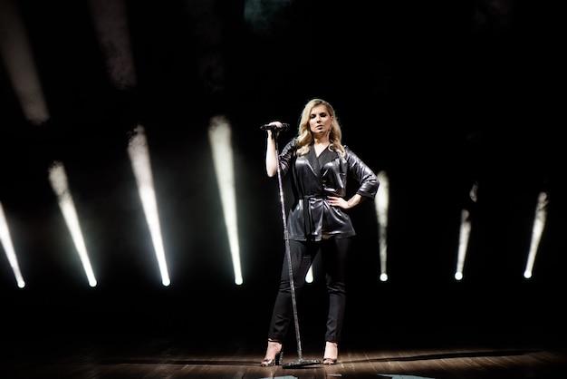 Uma jovem cantora de cabelo comprido, segurando um microfone com suporte e canta.