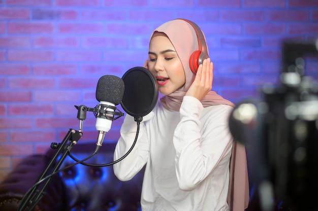 Uma jovem cantora muçulmana sorridente usando fones de ouvido com um microfone enquanto grava música em um estúdio de música com luzes coloridas.