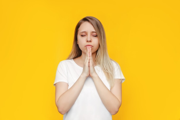Uma jovem caucasiana linda loira em uma camiseta branca ora com os olhos fechados e as mãos postas, agradecendo, fazendo um desejo, pedindo ajuda, esperança ou perdão, isolado em uma parede de cor brilhante amarela