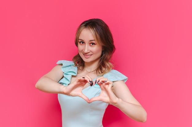 Uma jovem caucasiana, muito adorável, sorridente, de cabelos castanhos, em um vestido azul claro, formando um coração com as mãos isoladas em uma parede de cor rosa brilhante