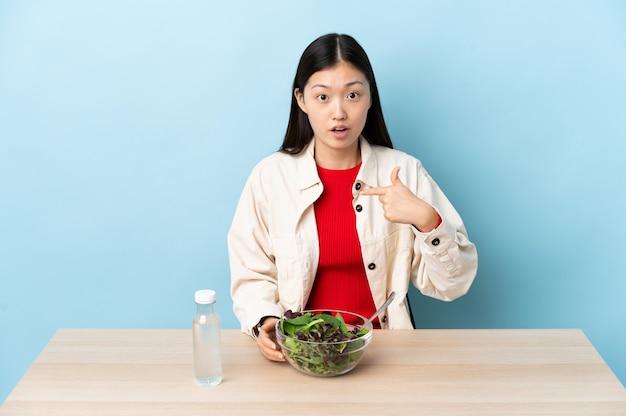 Uma jovem chinesa a comer uma salada a apontar para si mesma