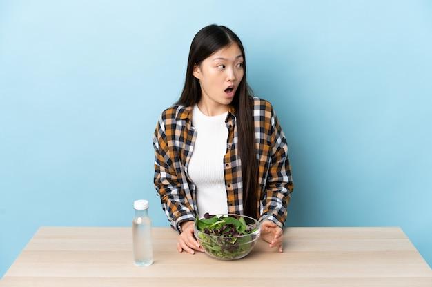 Uma jovem chinesa a comer uma salada a fazer um gesto de surpresa enquanto olha para o lado