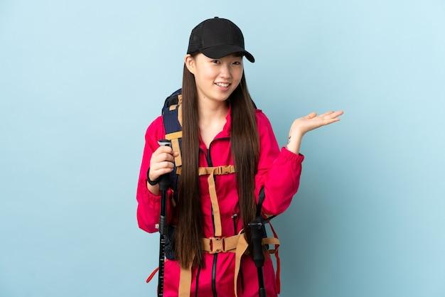 Uma jovem chinesa com mochila e bastões de trekking sobre uma parede azul isolada estendendo as mãos para o lado para convidar a vir