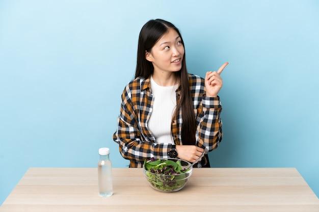 Uma jovem chinesa comendo uma salada apontando uma ótima ideia