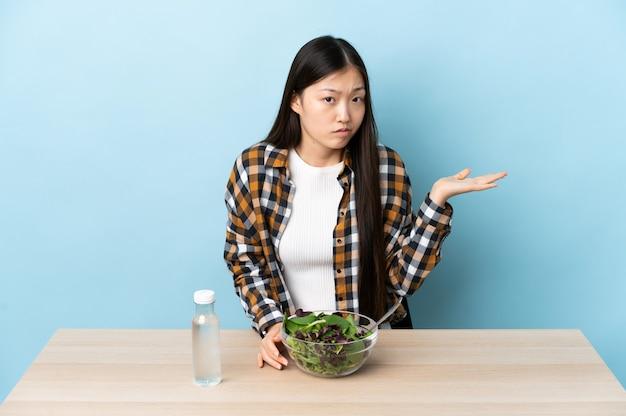 Uma jovem chinesa comendo uma salada e tendo dúvidas