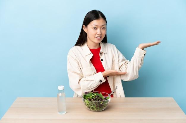 Uma jovem chinesa comendo uma salada, estendendo as mãos para o lado e convidando-a a vir