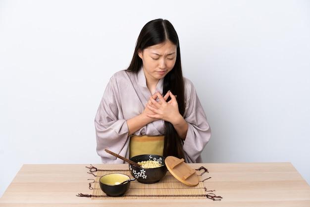 Uma jovem chinesa de quimono a comer macarrão com uma dor no coração