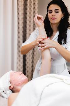 Uma jovem cliente com uma máscara de alginato no rosto está deitada na mesa de cosmetologia, a esteticista faz uma massagem manual nas mãos