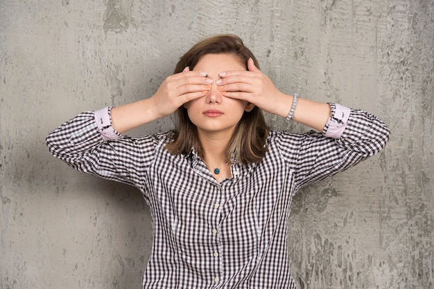 Uma jovem cobrindo os olhos com as mãos com uma bela manicure