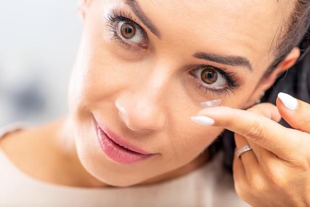Uma jovem coloca lentes de contato nos olhos.