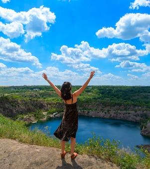 Uma jovem com as mãos abertas fica em uma colina acima de um lago pitoresco. conceito de liberdade. fototografia de estoque.
