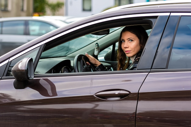 Uma jovem com cabelo comprido está sentada ao volante de um carro e olhando pela janela