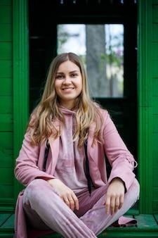 Uma jovem com cabelos loiros de aparência europeia está sentada na escada. menina de terno rosa e tênis