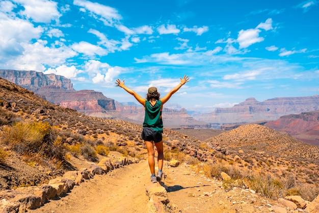 Uma jovem com camisa verde e braços abertos no trekking south kaibab trailhead. grand canyon