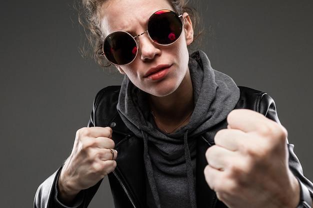 Uma jovem com características faciais ásperas, cabelos castanhos afagados, manicure brilhante, em uma bicicleta cinza, jaqueta preta, segura os óculos de sol com as mãos e mostra os punhos