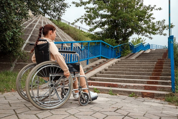 Uma jovem com deficiência está sentada em uma cadeira de rodas em frente à escada. o conceito de cadeira de rodas, pessoa com deficiência, vida plena, paralítico, pessoa com deficiência, cuidados de saúde, solidão.
