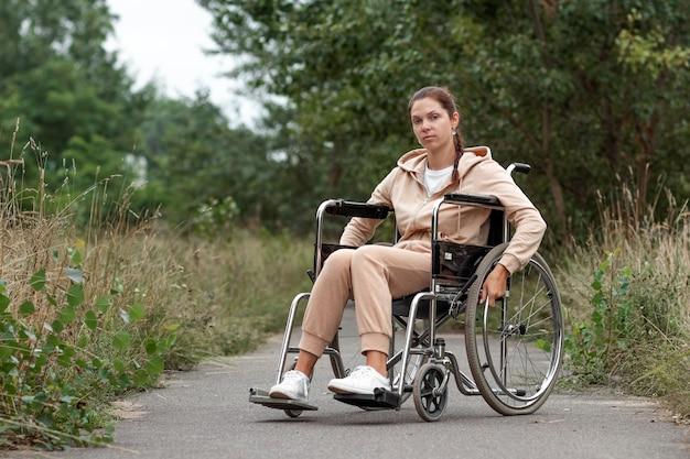 Uma jovem com deficiência está sentada em uma cadeira de rodas na rua. o conceito de cadeira de rodas, pessoa com deficiência, vida plena, paralítico, pessoa com deficiência, cuidados de saúde.
