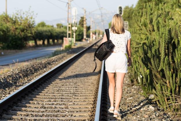 Uma jovem com longos cabelos castanhos caminhando perto da ferrovia