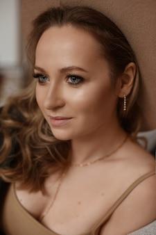 Uma jovem com maquiagem perfeita e olhos azuis profundos posando em ambientes fechados com um conceito de beleza e maquiagem da moda