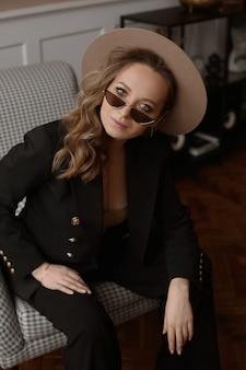 Uma jovem com maquiagem perfeita, usando óculos escuros da moda e um chapéu moderno, posando no interior ...