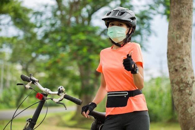 Uma jovem com máscara médica anda de bicicleta