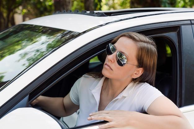 Uma jovem com óculos escuros olha curiosamente à frente da janela de seu carro branco moderno. retrato do estilo de vida de uma mulher dirigindo bem-sucedida. dirigindo e viajando de carro, há um engarrafamento à frente