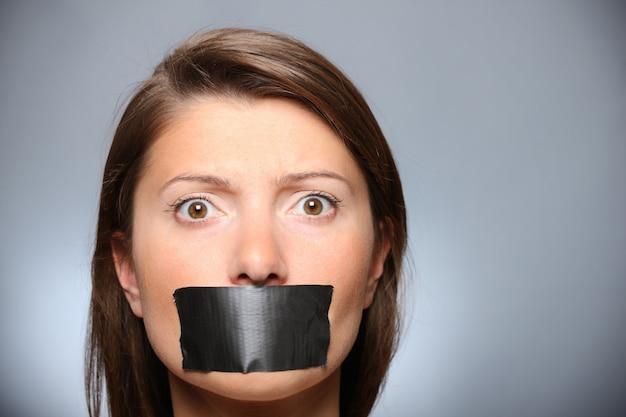 Uma jovem com os lábios cobertos por uma fita sobre um fundo cinza