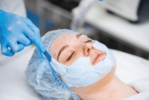 Uma jovem com problema de pele em uma clínica de cosmetologia. aplicação de máscara facial de alginato.