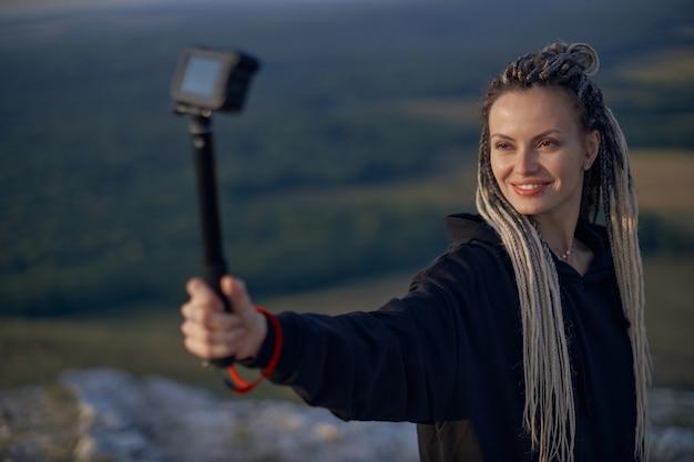 Uma jovem com rabo de cavalo grava um vlog sobre uma viagem no topo de uma montanha, o conceito ...