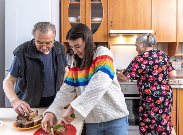 Uma jovem com seus pais está preparando o almoço na cozinha de casa.