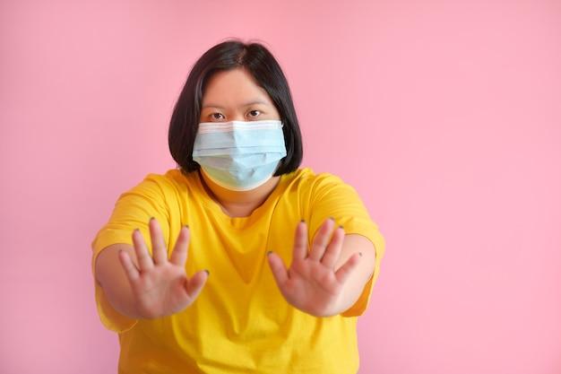 Uma jovem com síndrome de down use uma máscara para se proteger contra o coronavírus covid-19. ela é uma estudante de paralisia cerebral chamada síndrome de down. ela usava um vestido amarelo