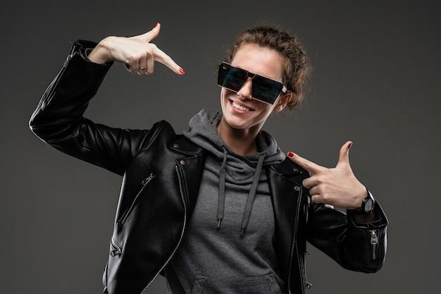 Uma jovem com traços faciais ásperos, cabelos castanhos tapados, manicure brilhante, em uma bicicleta cinza, jaqueta preta, segura óculos de sol com as mãos e mostra-se com os dedos