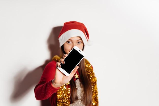 Uma jovem com um boné vermelho na cabeça mostra a tela do telefone, atmosfera de natal