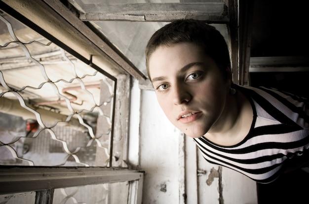 Uma jovem com um cabelo curto fica perto da janela