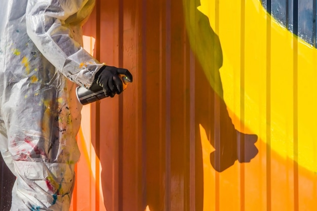 Uma jovem com um casaco branco com manchas de tinta grafite em cerca de ferro com nervuras