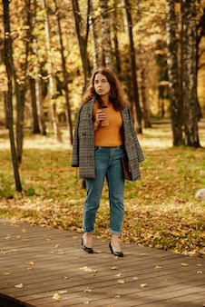 Uma jovem com um casaco caminha pelo parque de outono