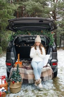 Uma jovem com um chapéu de lã está sentada no porta-malas de um carro segurando uma xícara de chá quente