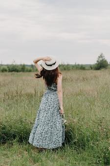 Uma jovem com um chapéu de palha em um campo verde
