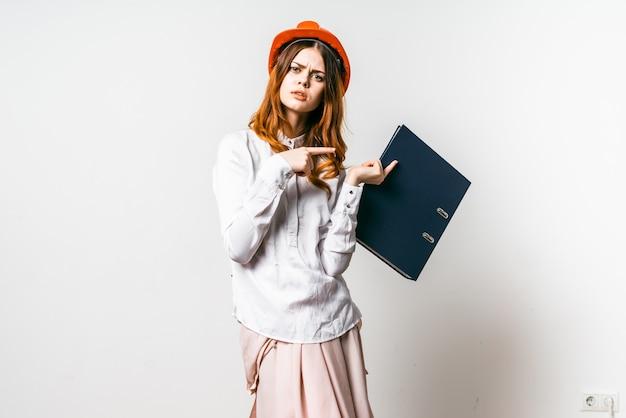 Uma jovem com um chapéu laranja com dúvida aponta para uma pasta com documentos. isolado em fundo branco