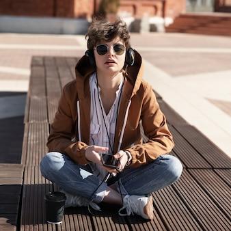 Uma jovem com um corte de cabelo curto elegante senta-se em um banco e ouve música em fones de ouvido.