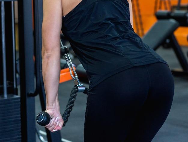 Uma jovem com um espólio sexy em calças pretas justas, envolvida em uma academia de ginástica