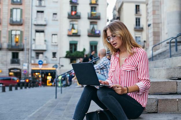 Uma jovem com um laptop sentada na escada, perto da universidade