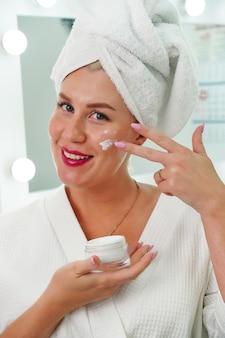 Uma jovem com um roupão de banho e uma toalha na cabeça no banho realiza uma pele facial profissional ca ...