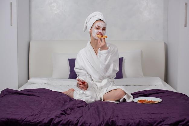Uma jovem com um roupão e uma toalha deliciosamente come pizza e bebe vinho enquanto está sentada em casa na cama foto de alta qualidade