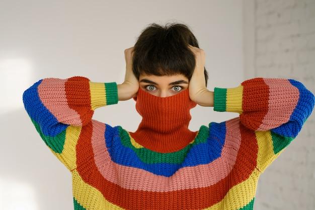 Uma jovem com um suéter de arco-íris multicolorido brilhante esconde o rosto e cobre as orelhas com as mãos.