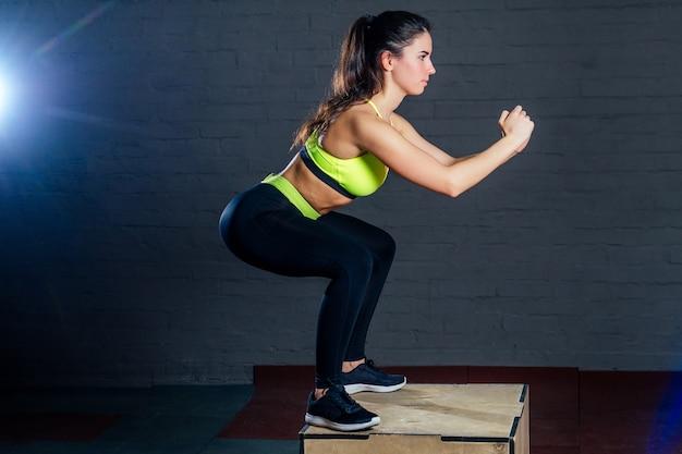 Uma jovem com um sutiã esportivo verde e calça preta pula em uma caixa contra um fundo de tijolos pretos.