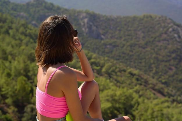 Uma jovem com um top rosa brilhante sentada no topo de uma montanha com uma bela vista das montanhas e do mar mediterrâneo no sul da turquia