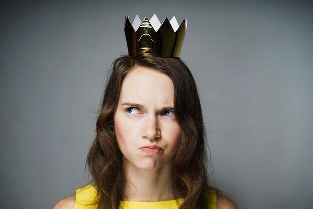 Uma jovem com um vestido amarelo olha pensativa, está infeliz com alguma coisa, uma coroa de ouro na cabeça