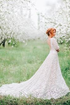 Uma jovem com um vestido branco está em um jardim florido